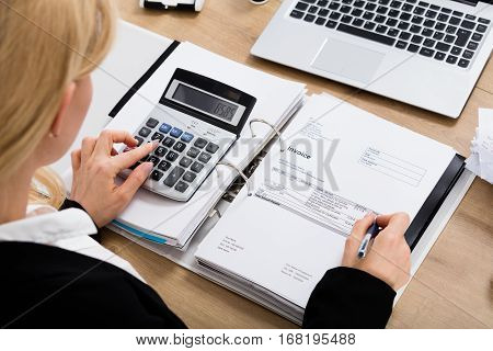High Angle View Of A Accountant Woman Calculating Finance Invoice Using Calculator In Office