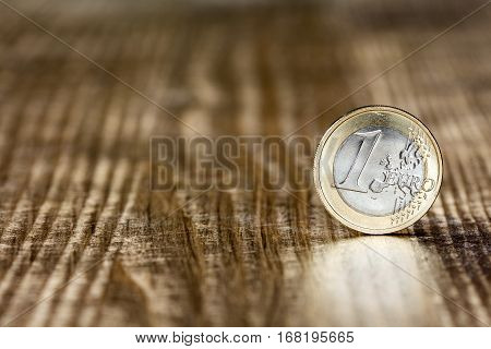 One Euro coin on the wooden table surface