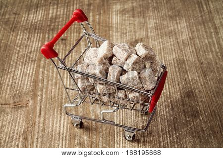 Shopping cart full of brown cane sugar on wooden background