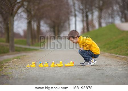 Adorable Child, Boy, Playing In Park With Rubber Ducks, Having Fun