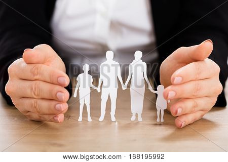 Close-up Of A Businesswoman Protecting Family Papercut On Wooden Desk