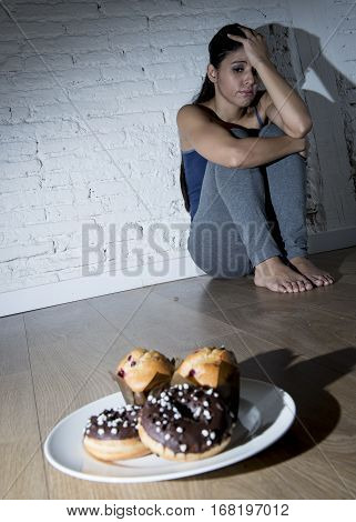 unhealthy sugar donuts and muffins and tempted young woman or teenager girl sitting on ground worried about overweight in diet and weight loss obsession in unhealthy nutrition concept