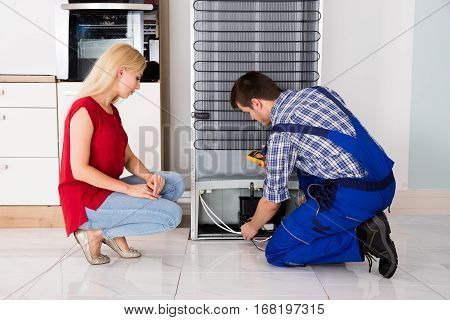 Woman Looking At Male Repairman Checking Fridge With Digital Multimeter At Home
