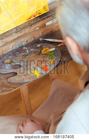 Art is life. Close up of an elderly thoughtful handsome artist sitting in painting class and working while painting.