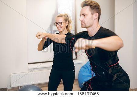 Female Coach Training Man With Ems