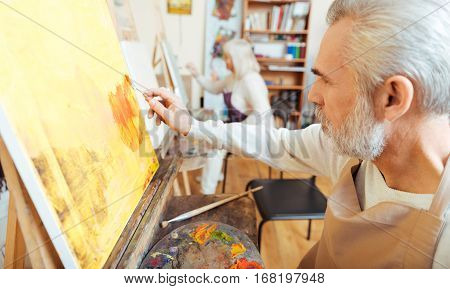 1. Inspirational time. Concentrated talented elderly artist painting a picture while working in painting class and enjoying his hobby.