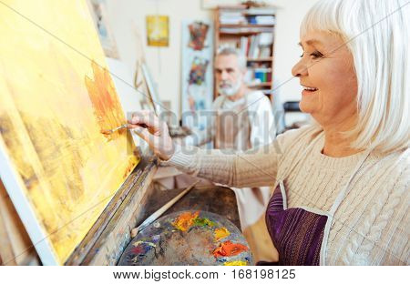 Time for hobby. Female pretty elderly artist working in painting class and enjoying her hobby while painting.