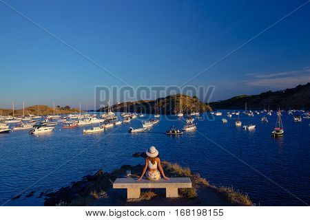 A girl in a hat sitting on a bench looking at Gallipoli bay with yachts under a clear blue sky