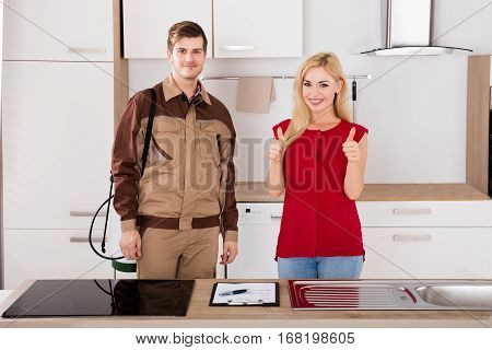 Woman Showing Thumbs Up With Pest Control Exterminator Service Worker Standing In Kitchen