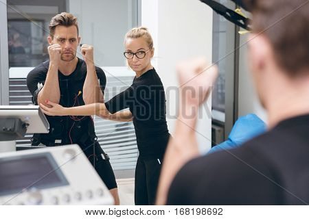 Sportsman Teached By Personal Trainer In Front Of Mirror