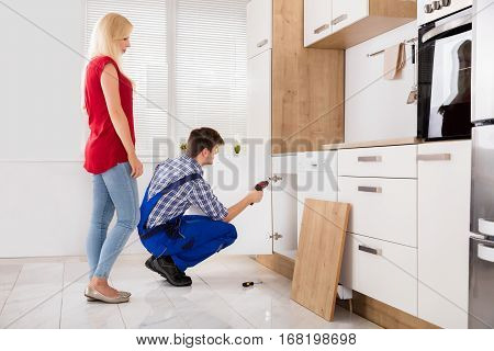 Repairman Fixing The Door Of The Kitchen Sink In Front Of Young Woman