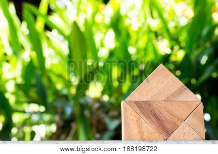 Wooden toy as dream house concept with blurred green blackground
