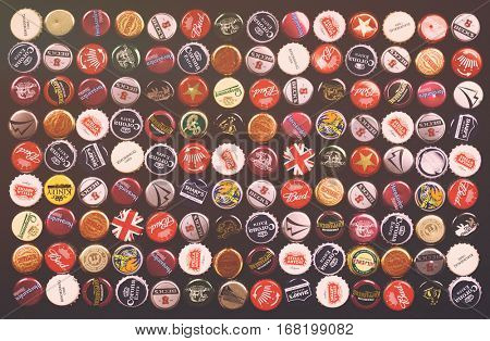 SOUTHAMPTON, UK - 21 Jan 2017: A background of bottle caps from a variety of popular beers, lagers and ciders from around the world. Filtered to look like an old 1970s style pub poster.