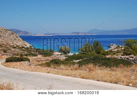 HALKI, GREECE - JULY 24, 2016: Looking down towards Kania beach on the Greek island of Halki. Once a deserted cove, the beach now has tourist facilities including a taverna and sunbeds.