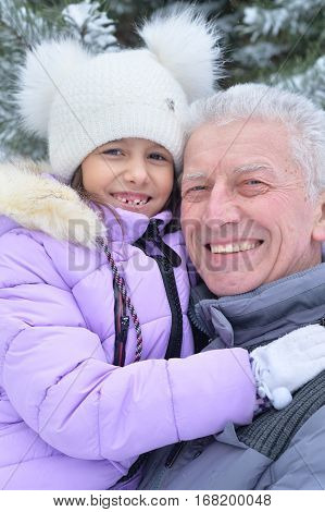 grandfather with granddaughter smiling, posing outdoors in winter