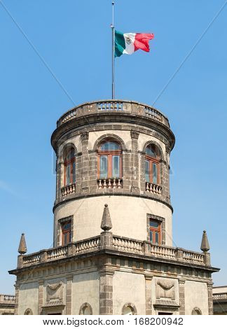 The Caballero Alto tower on top of Chapultepec Castle in Mexico City with a waving mexican flag