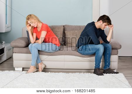 Sad Angry Cheating Couple Sitting Back To Back On Sofa At Home
