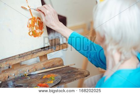 poster of Delicious painting. Female elderly concentrated artist painting picture and using putty knife while working in studio.