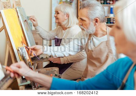 Productive cooperation. Three professional talented elderly artists spending time in painting studio while painting and enjoying their hobby