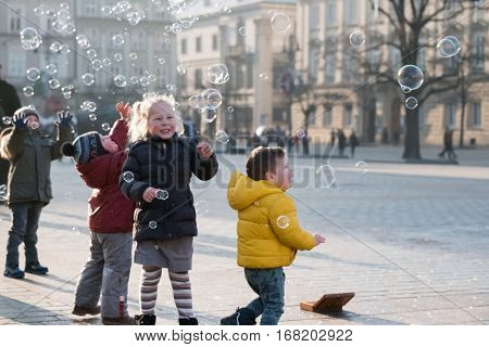 Krakow, Poland - December 20, 2016: Children age 4-5 years playing with soap bubbles on the square at day time