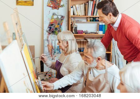 poster of Talented teacher. Concentrated handsome young artist controlling his colleagues while sitting in painting class and drawing together
