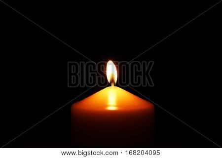 Big single candle in the center of the photo on dark background. Memory calm glow light closeup. Romantic or RIP darkness template