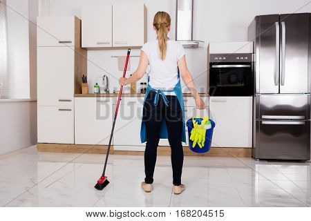 Rear View Of Young Housemaid Service Woman With Cleaning Equipment Standing In Kitchen