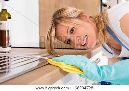 Close-up Of Smiling Young Janitor Woman Cleaning Dirty Kitchen Worktop With Rag
