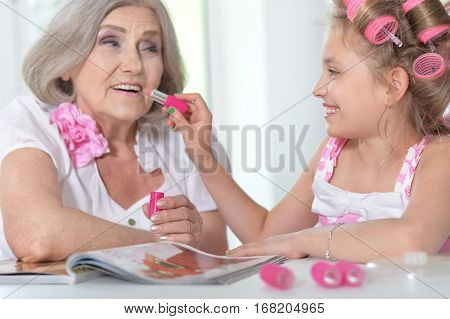 granddaughter making make up to her granny, close up