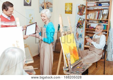 Be proud. Handsome young smiling man giving artists diploma to woman while spending time in painting school and working as a teacher.