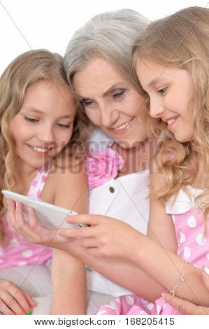 Portrait of a granny with her granddaughters using smartphone