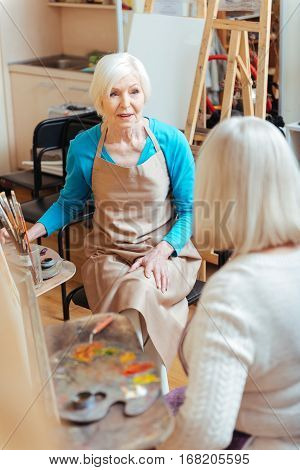 Common activity. Elderly happy ambitious ladies talking and spending time in painting class while drawing. poster