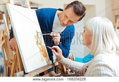 Perfect result. Serious handsome concentrated man teaching elderly woman while drawing pictures in painting school and enjoying their hobby.