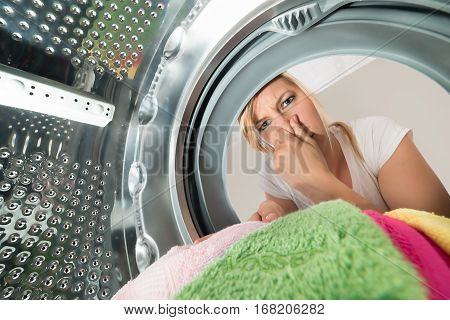 Close-up Of Young Woman Inserting Stinky Clothes In Washing Machine