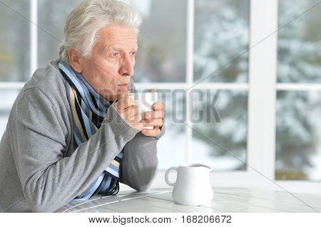manure man drinking tea sitting near window