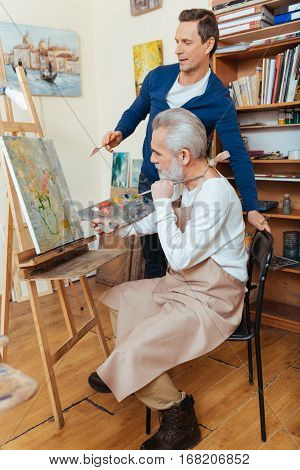 Perfect worker. Ambitious handsome young artist helping elderly man while he painting and spending time in painting studio