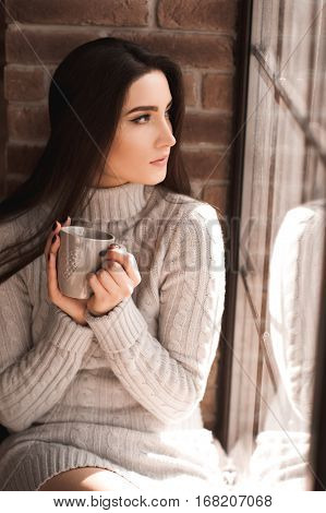 Beautiful brunette girl 20-24 year old holding cup with tea wearing knitted sweater sitting on windowsill. Looking at window. 20s. Good morning.
