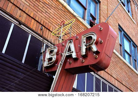 Old neon sign advertises a coctail on exterior of old building. Sign is in Montana and white letters spell bar.