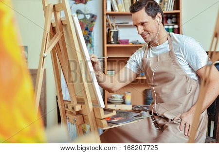 Harmony and inspiration. Inspired young handsome artist painting picture on a canvas while listening to music and working in painting studio.
