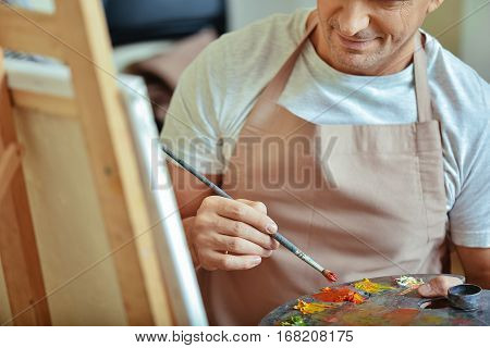 Artistic equipment. Close up of concentrated handsome young artist holding a brush and palette while painting and sitting in painting studio.