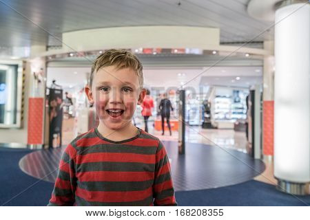 Happy and excited boy in front of a store eager to go in shopping.