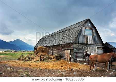 Storm clouds cover sky over rustic log barn in Happy Valley Montana. Two horses stand ready to brave the weather.