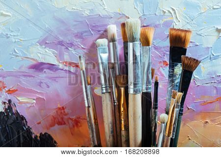 Nice combination. Close up of painting brushes and canvas colorful canvas with picture.