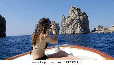Woman taking a photo in a Boat Travel at Faraglioni Cliffs, Capri, Italy
