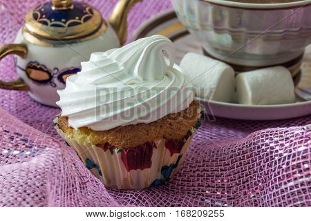 Muffin, decorated with whipped protein cream, on the background cup of  tea  and teapot