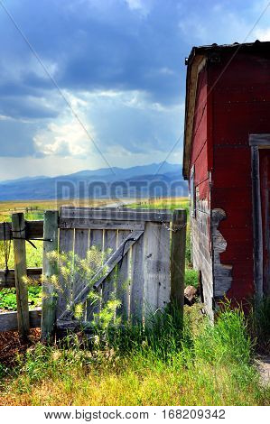 Rustic gate and old building seperate you from a road leading to the Gallatin Mountains in Happy Valley Montana.
