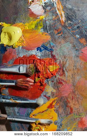 For a good painting. Top view of palette and painting brushes lying on it with paints being mixed.