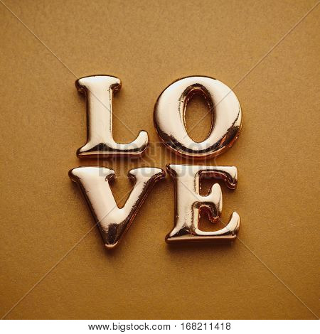 Single word 'love' in gold lettering. Gold letters spelling LOVE. Letters forming word LOVE written on golden background.