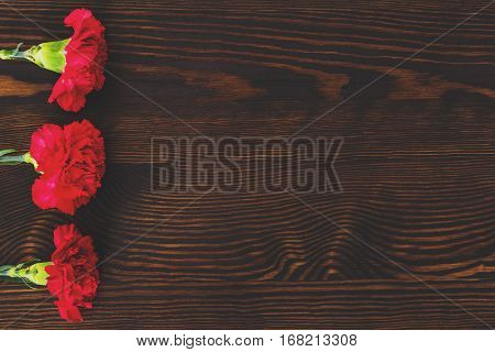 Red Carnations On Wood Table