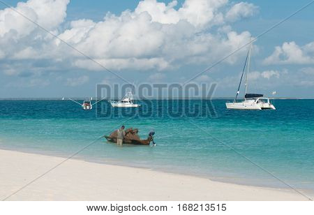 ZANZIBAR, TANZANIYA- JULY 17: tman near his boat with traps for crabs and yachts on the sea on July 17, 2016 in Zanzibar